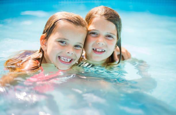 portrait of two little girls in pool. - organizm wodny zdjęcia i obrazy z banku zdjęć