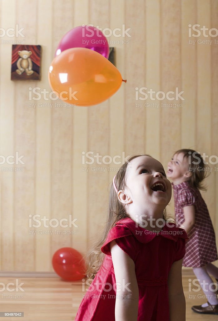 Portrait of two little girls playing with airy balls stock photo