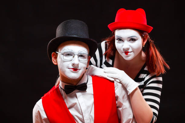 Portrait of two mime artists, isolated on black background. Woman and man look at camera. Symbol of happy marriage, sweet couple, family portrait stock photo