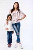 portrait of two adorable mixed race sisters isolated on white in studio