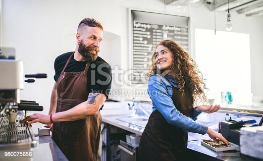 1003493404istockphoto Portrait of two professional young baristas behind a counter in a cafe. 980075656
