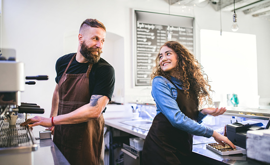 1003493404 istock photo Portrait of two professional young baristas behind a counter in a cafe. 980075656