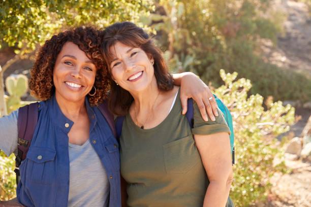 porträt von zwei seniorinnen, die gemeinsam auf dem weg ins land wandern - freundin stock-fotos und bilder
