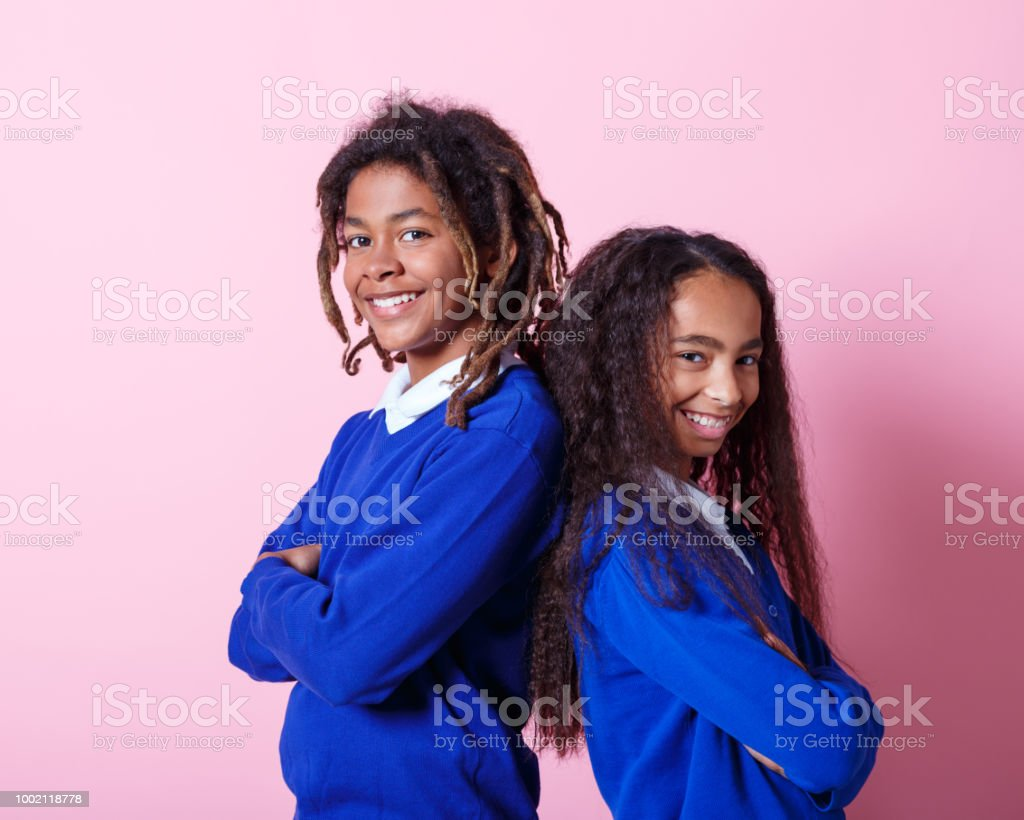 Portrait of two smiling afro amercian teenage students Two afro American teenagers wearing school uniforms standing back to back with arms crossed and smiling at camera. Studio shot, pink background. 10-11 Years Stock Photo