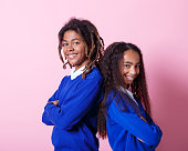 Two afro American teenagers wearing school uniforms standing back to back with arms crossed and smiling at camera. Studio shot, pink background.