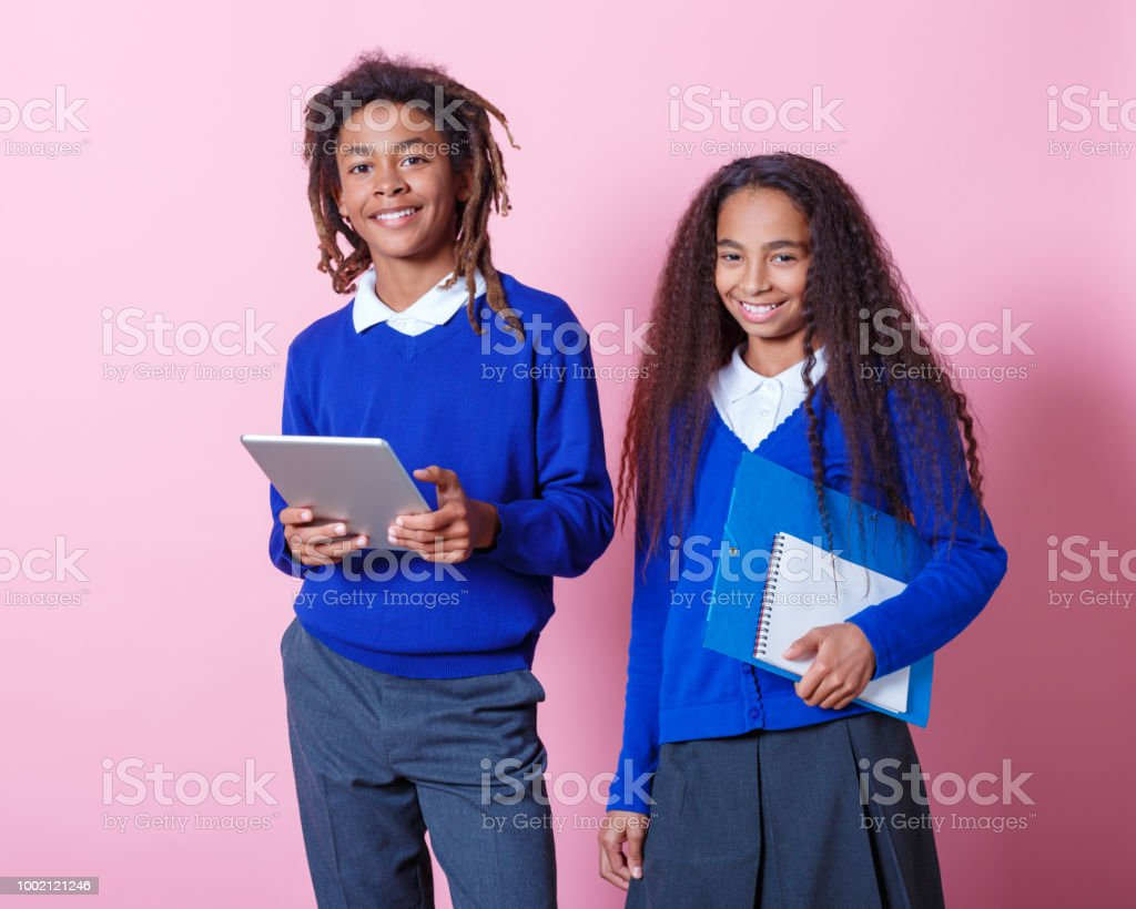 Portrait of two smiling afro amercian teenage students Two afro American teenagers wearing school uniforms holding workbook and digital tablet, smiling at the camera. Studio shot, pink background. 10-11 Years Stock Photo