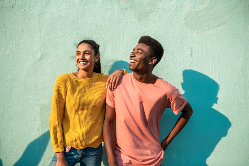 Portrait of Young couple. They are looking away laughing and leaning on light blue wall