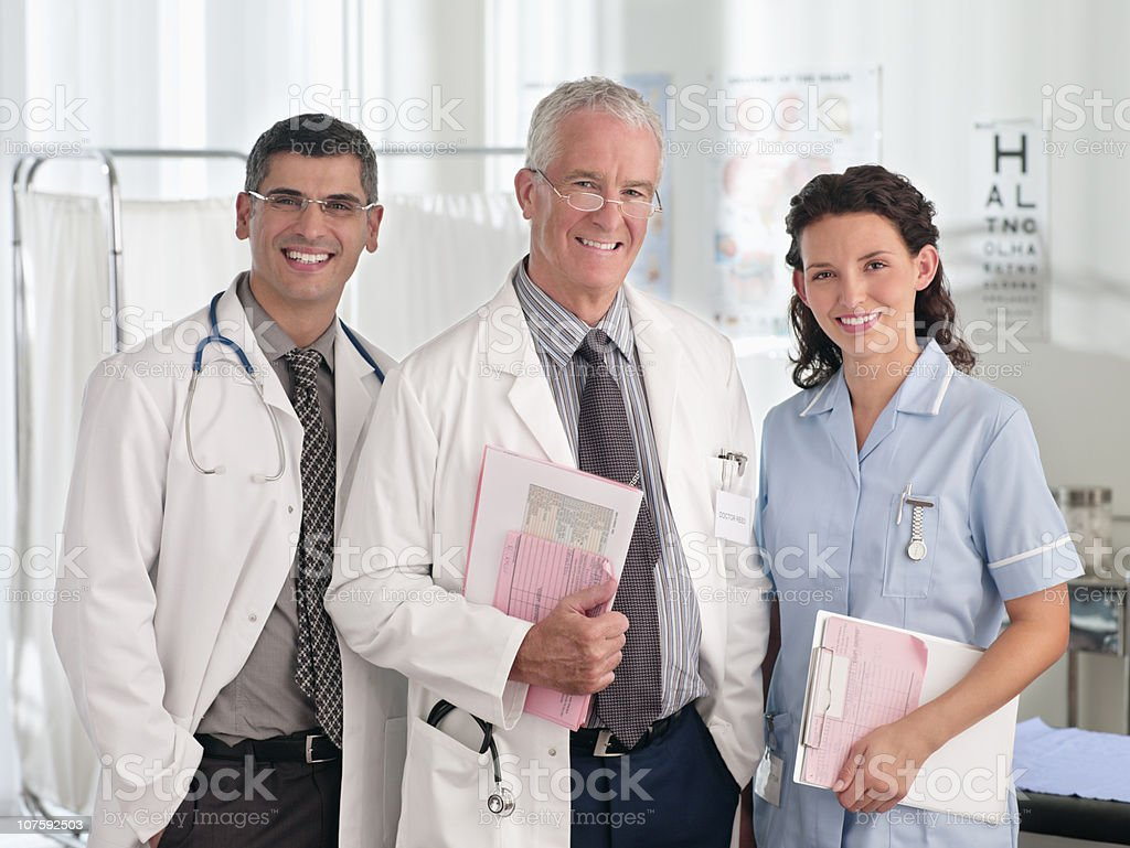 Portrait of two smiling male doctors with female nurse holding medical report royalty-free stock photo