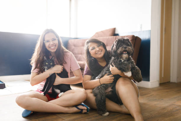 Portrait of two smiling young women sitting on living room floor holding a cat and a dog stock photo