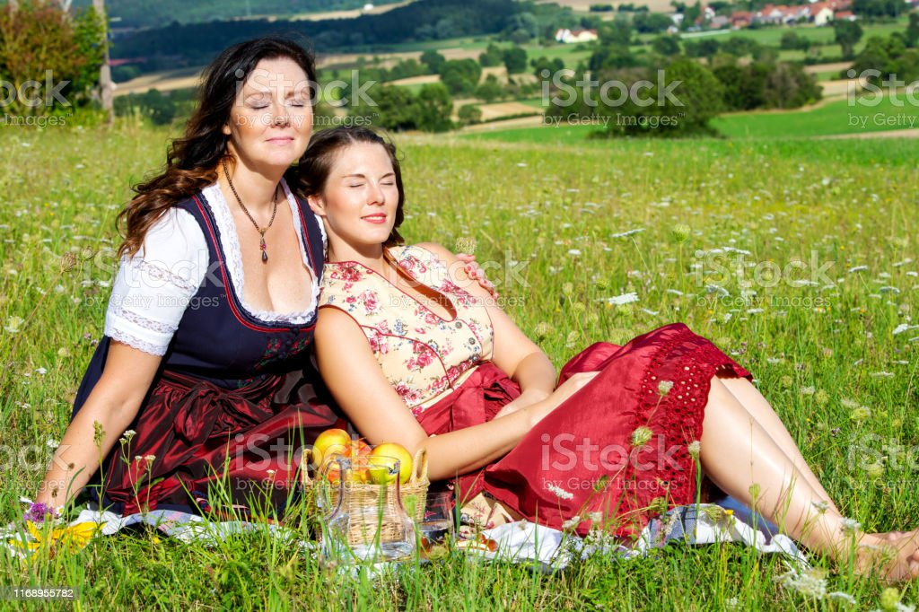 portrait of two woman in dirndl sitting on blanket in meadow and...