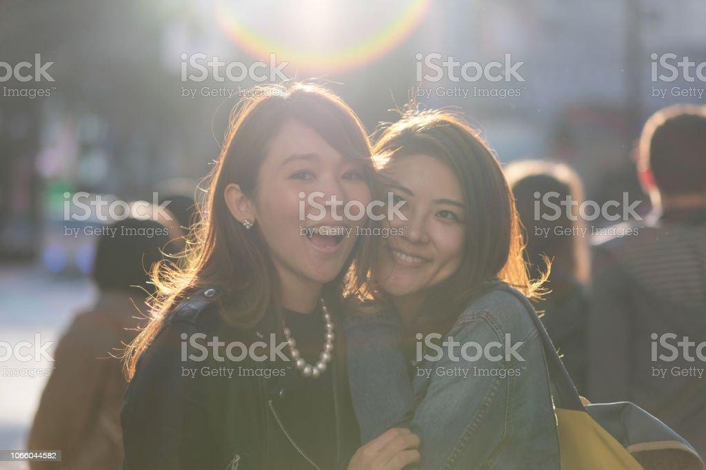 0075485b3d0456 Porträt von zwei Frauen auf der Straße gegen Licht Lizenzfreies stock-foto