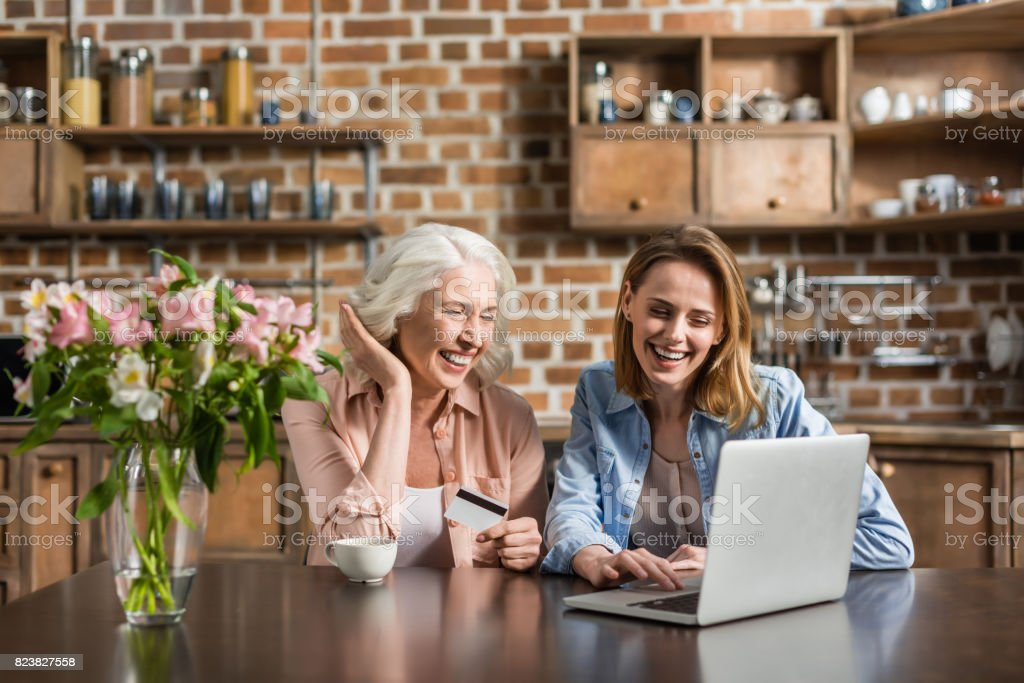Portrait of two women, senior and young using laptop and credit card doing online shopping - Royalty-free Adult Stock Photo