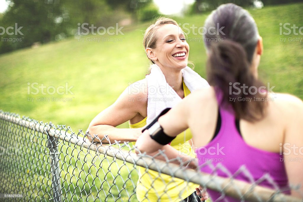 Portrait of two women talking after the workout in park. stock photo