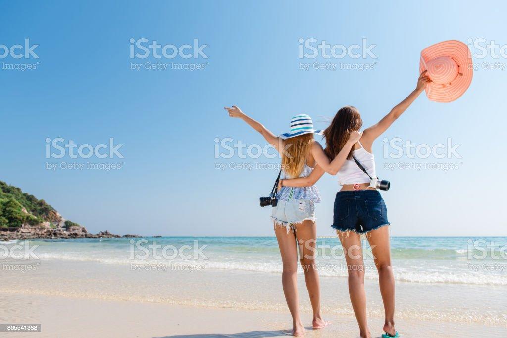 Portrait de deux jeunes amis femmes asiatiques marcher sur le bord de mer rebrousser chemin à rire de la caméra. Multiraciales jeunes femmes se promenant le long d'une plage. photo libre de droits