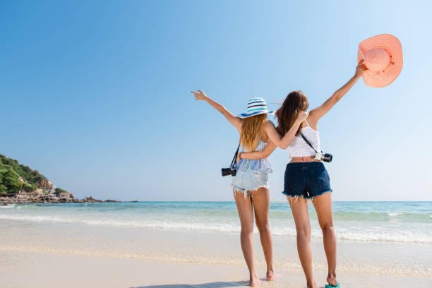 Portrait of two young asian female friends walking on the sea shore turn back at camera laughing. Multiracial young women strolling along a beach. stock photo
