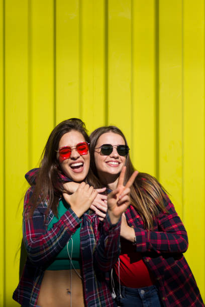 Portrait of two young happy women friends standing outdoor over yellow wall stock photo