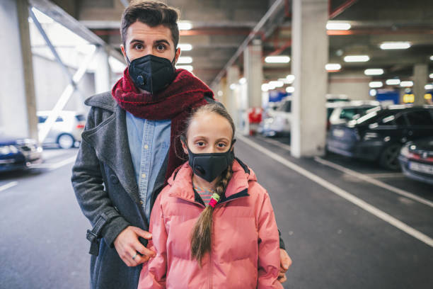 Portrait of two young people protecting their health with anti-pollution face masks Young people in big car park building wearing anti-smog masks for health and lungs protection antipollution stock pictures, royalty-free photos & images