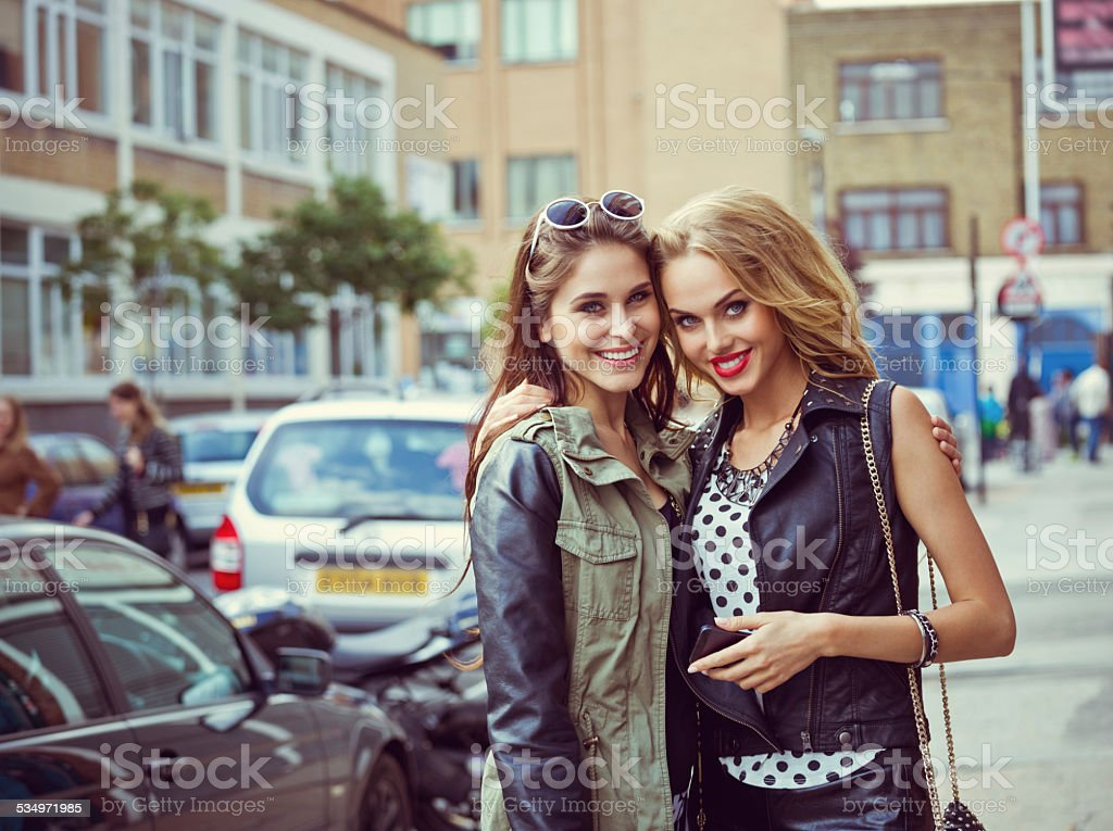 Portrait of two young women on the street Portrait of two happy young women on the street, smiling at camera. 16-17 Years Stock Photo