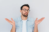 istock Portrait of uncertain young stylish stubble man with trendy round glasses wears demin blue shirt, shrugs shoulders being puzzled or confused. Caucasian unsure male make gestures doubtfully with hands. 951331792