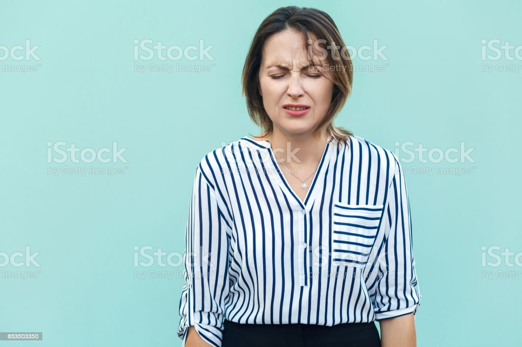 Portrait of unhappy and depressed woman with blonde hair feeling ashamed or sick, keeping eyes closed. Human face expressions and emotions concept. stock photo