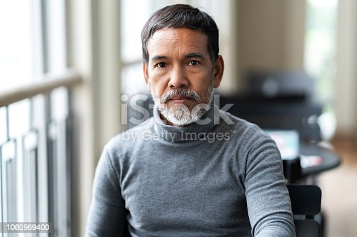 istock Portrait of unhappy angry mature asian man with stylish short beard looking at cemera with negative suspicious. Casual retired hispanic people feeling worry or unpleasant at outside cafe concept. 1060969400