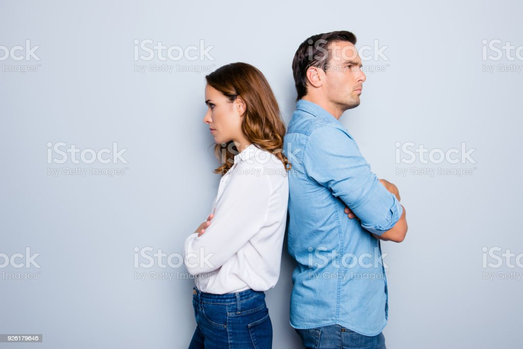 Portrait of unhappy frustrated couple standing back to back not speaking to each other after an argument while standing on grey background. Negative emotion face expression reaction stock photo