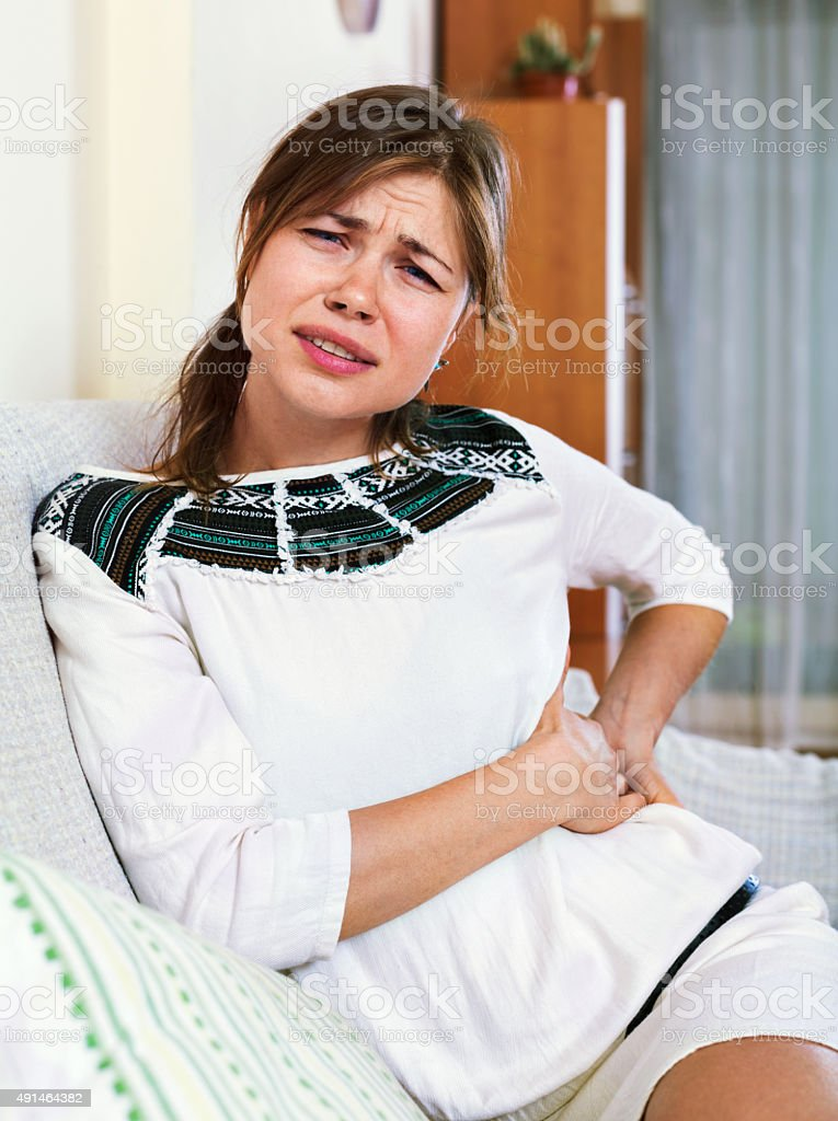 Portrait of unhappy girl having pangs of belly-ache stock photo