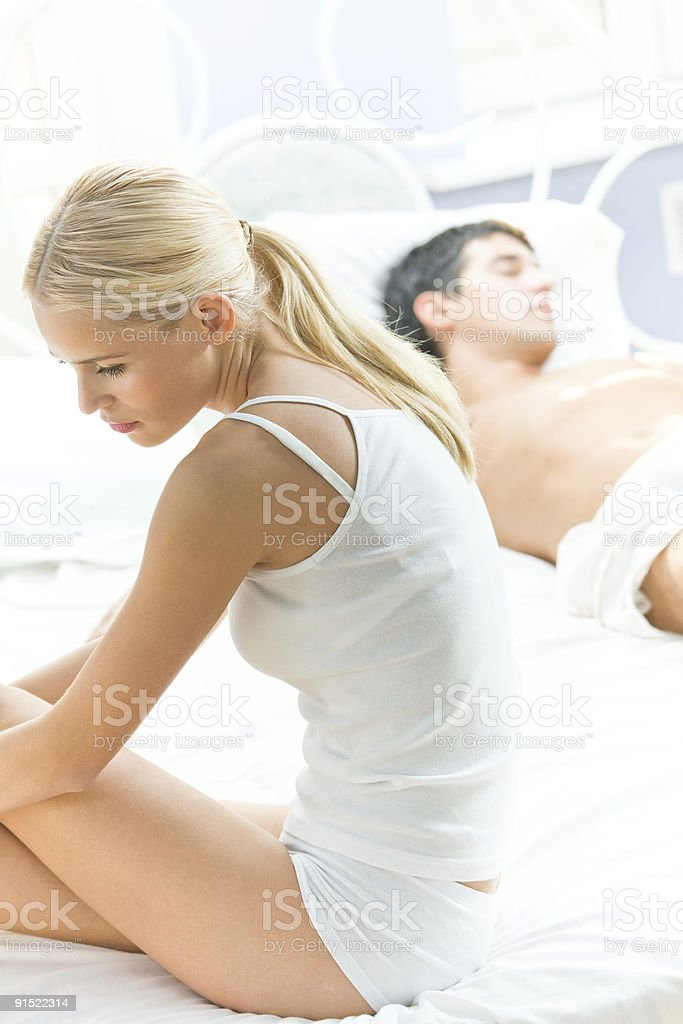 Portrait of unhappy young couple in bedroom stock photo
