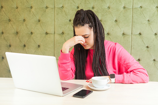 Portrait of unhappy young girl freelancer with black dreadlocks hairstyle in pink blouse sitting and working on laptop, closed eyes and trying to stop crying hold fingers on the eyes,