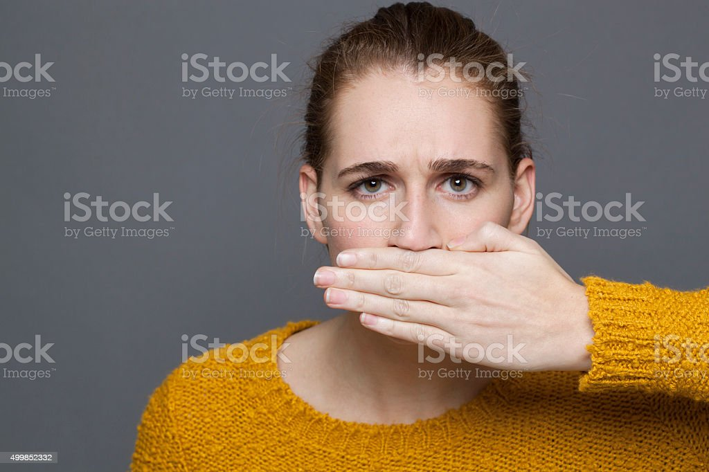 portrait of unhappy young woman covering her mouth for frustration stock photo