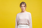 istock Portrait of unhappy young woman with messy blonde hair in casual beige blouse, isolated on yellow background 1188189630