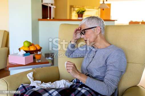 Shot of a senior woman blowing her nose with a tissue at home. Senior woman in spectacles blowing her nose. Feeling absolutely dreadful. I need some immune system support. A senior woman blowing her nose. Elderly woman having a cold, blowing nose