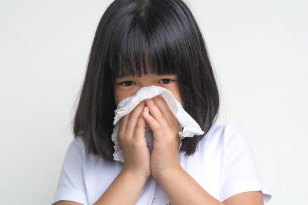 porträt der ungesunden kranken asien-kind mädchen, die mit serviette stehen, schließen ihre nase vor allergie oder rhinitis. unglückloses krankes kind, das an laufender nase leidet und niest und ihre nase auf weißem hintergrund blasen - schnäuzen stock-fotos und bilder