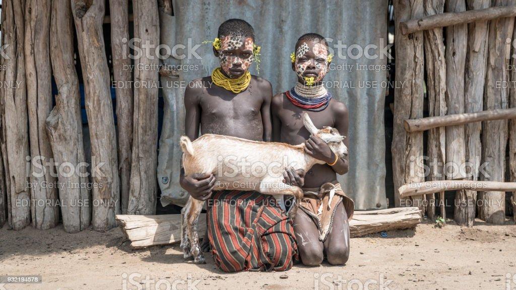 Portrait of unidentified Karo tribe children holding a goat, Colcho, Omo Valley, Ethiopia. stock photo