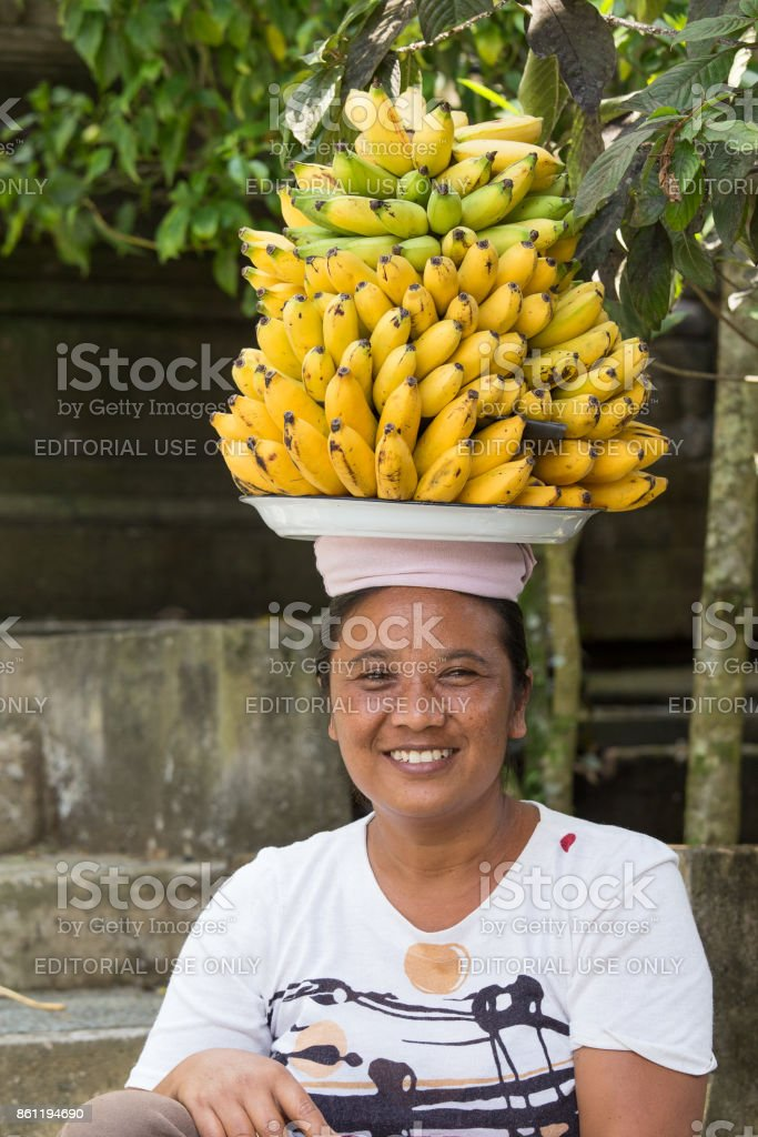 Portrait of unidentified woman together with bananas on her head on the market by the water temple of Tirta Empul. BALI, INDONESIA stock photo