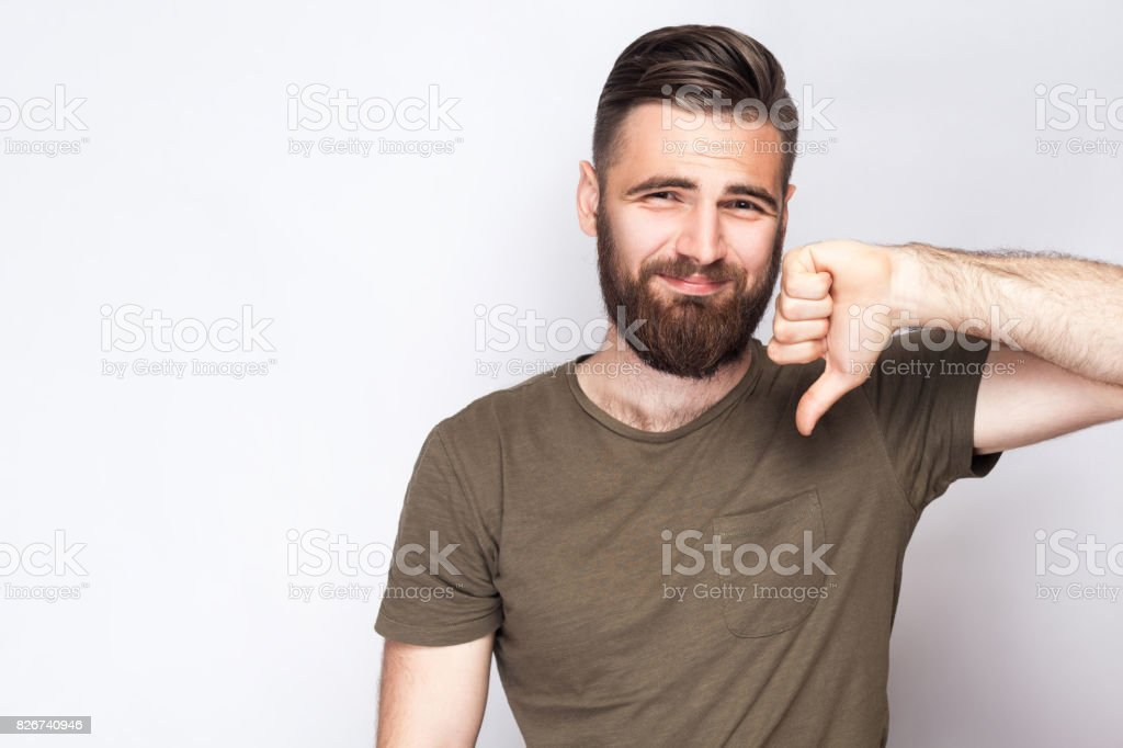 Portrait of unsatisfied bearded man with thumbs down and dark green t shirt against light gray background. stock photo