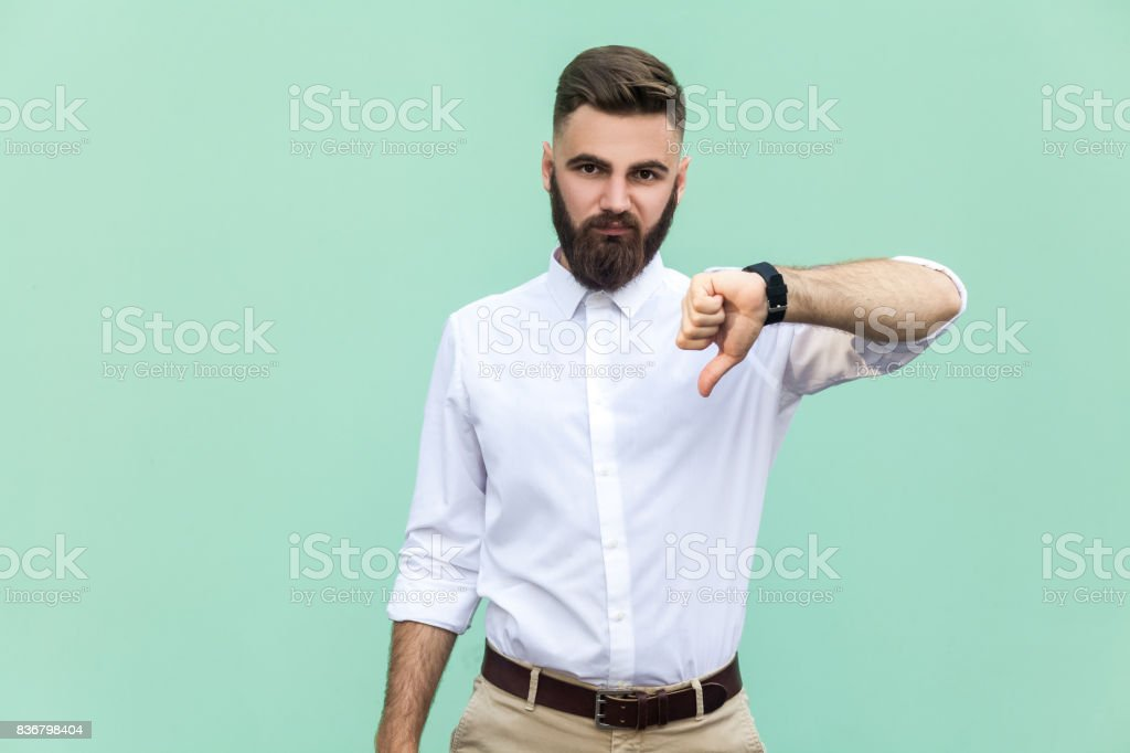 Portrait of unsatisfied bearded man with thumbs down and white shirt against light green background. Studio shot. stock photo