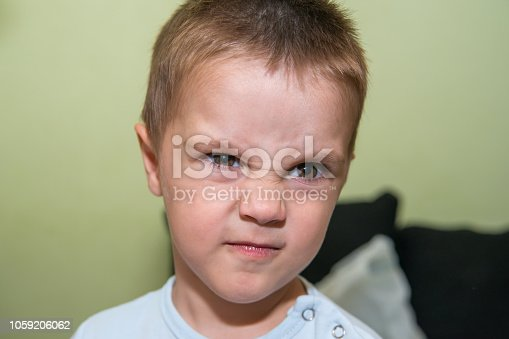 istock Portrait of upset and angry boy 1059206062