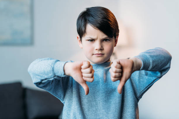 portrait of upset boy showing thumbs down looking at camera at home - thumbs down stock photos and pictures