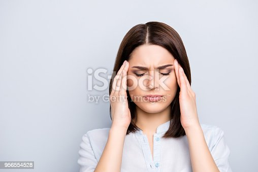 istock Portrait of upset, sad, pretty, nice, charming, stylish woman in shirt having head ache, stress, troubles, touching temples with fingers and close eyes, standing over grey background 956554528