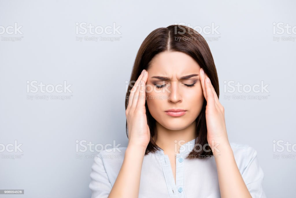Portrait of upset, sad, pretty, nice, charming, stylish woman in shirt having head ache, stress, troubles, touching temples with fingers and close eyes, standing over grey background stock photo
