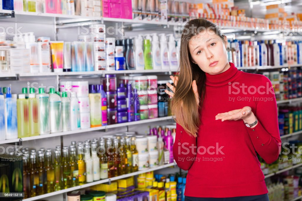 Portrait of upset woman who is dissatisfied of quality her hair in the store. royalty-free stock photo