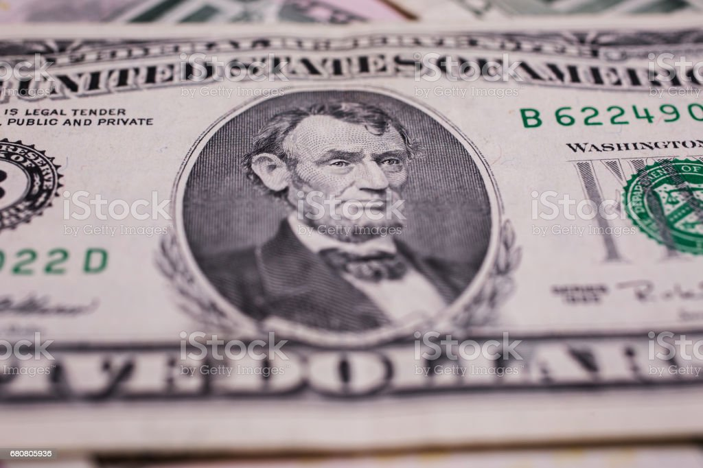 Portrait of US President Abraham Lincoln on the five dollar bill, background of the money, five dollar bills front side obverse. background of dollars, close up stock photo