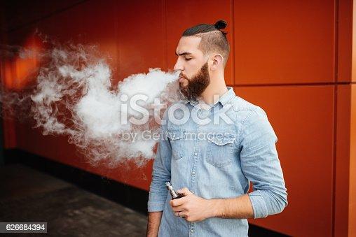 689660424 istock photo Portrait of vaper vaping a vaporizer outdoors. Safe smoking. 626684394