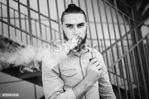 689660424 istock photo Portrait of vaper vaping a vaporizer outdoors. Safe smoking. 626684836