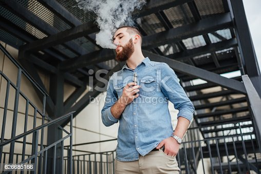 689660424 istock photo Portrait of vaper vaping a vaporizer outdoors. Safe smoking. 626685166