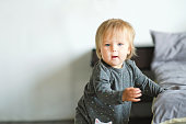 Portrait of very sweet little child. 1 year old baby stands next to the bed