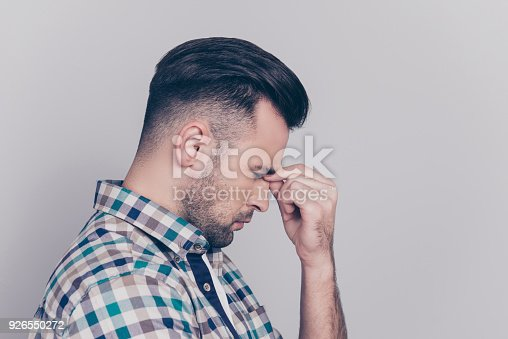 534891769 istock photo Portrait of very upset man touching nose between closed eyes, having problem with work, worry about conflict with his lover, feeling headache, eyes pressure, standing over grey background 926550272