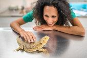 Portrait of veterinarian touching lizard in clinic.