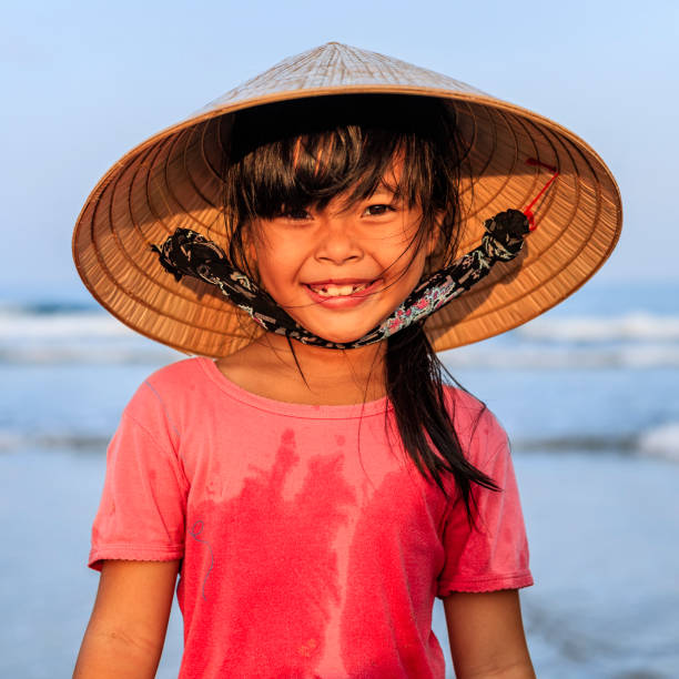 Portrait of Vietnamese little girl on the beach, Vietnam Portrait of Vietnamese little girl standing on the beach, Vietnam vietnamese culture stock pictures, royalty-free photos & images